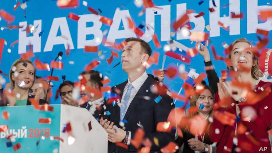Russian opposition leader Alexei Navalny, right, and his wife Yulia, left, celebrate during a meeting that nominated him for the presidential election race in Moscow, Russia, Dec. 24, 2017.