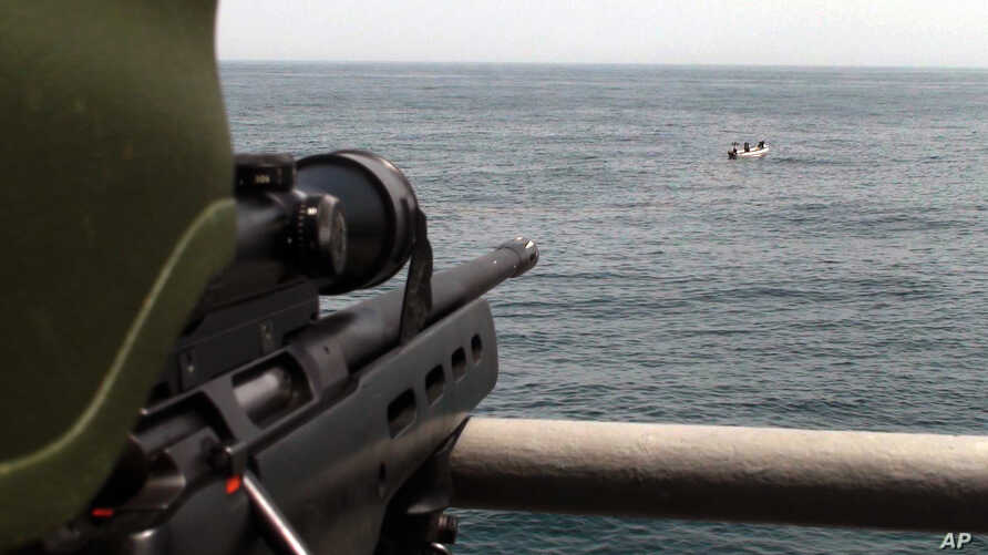 A Turkish commando, left, points his rifle toward five pirates surrounded in the Gulf of Aden
