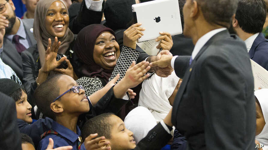 President Barack Obama greets children from Al-Rahmah school and other guests during his visit to the Islamic Society of Baltimore in Baltimore, Maryland, Feb. 3, 2016.