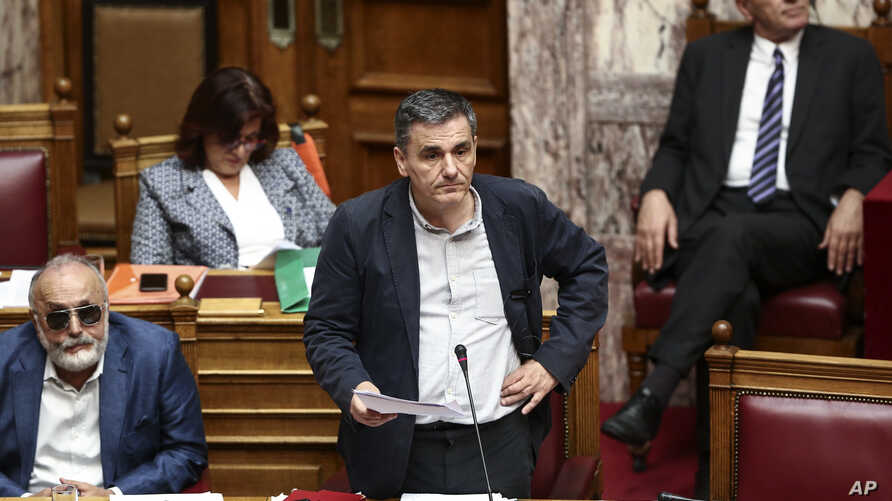 Greece's Finance Minister Euclid Tsakalotos (C) pauses during a parliamentary session in Athens, May 22, 2016. Greek lawmakers voted on a bill ahead of a Eurogroup meeting next week which is expected to unlock bailout funds for the country.