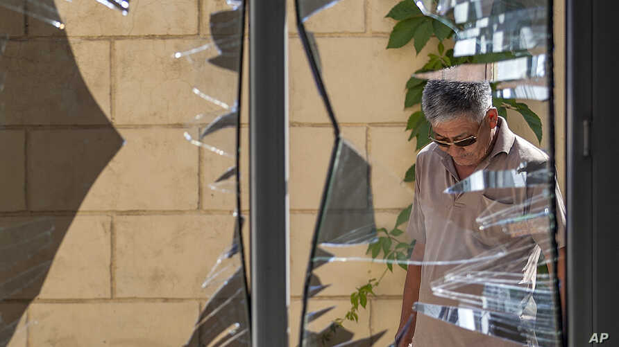 FILE - A Chinese Embassy employee examines broken windows at the embassy after a suicide bombing in Bishkek, Kyrgyzstan, Aug. 30, 2016. The bombing highlighted the expanding threat of an ethnic Uighur militant group that has sought for decades to est...