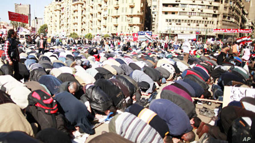 Demonstrators pray before a protest demanding the army to hand power to civilians, at Tahrir square in Cairo, January 27, 2012.
