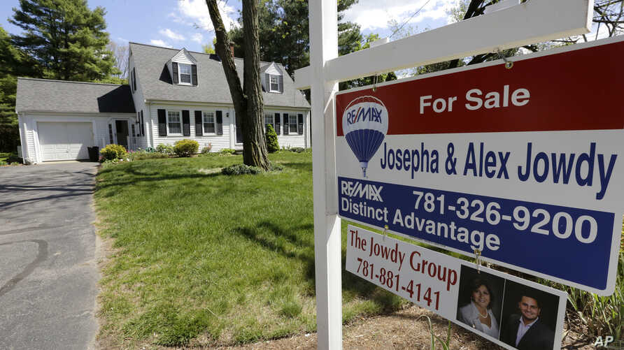 """A """"For Sale"""" sign stands in front of a house in Walpole, Mass. On Thursday, July 7, 2016, Freddie Mac reports on the week's average U.S. mortgage rates."""