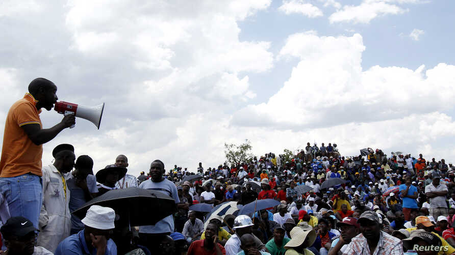Striking miners listen to an address by their leader at the AngloGold Ashanti mine in Carletonville, northwest of Johannesburg October 19, 2012.