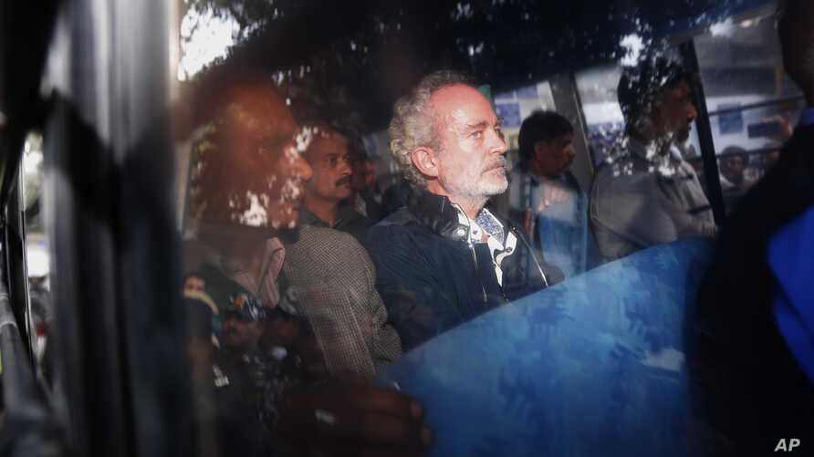 Christian James Michel, center, a British man accused of bribery in a $670 million helicopter deal between India and an Italian defense company returns after appearing before a Central Bureau of Investigation court in New Delhi, Dec.5, 2018.