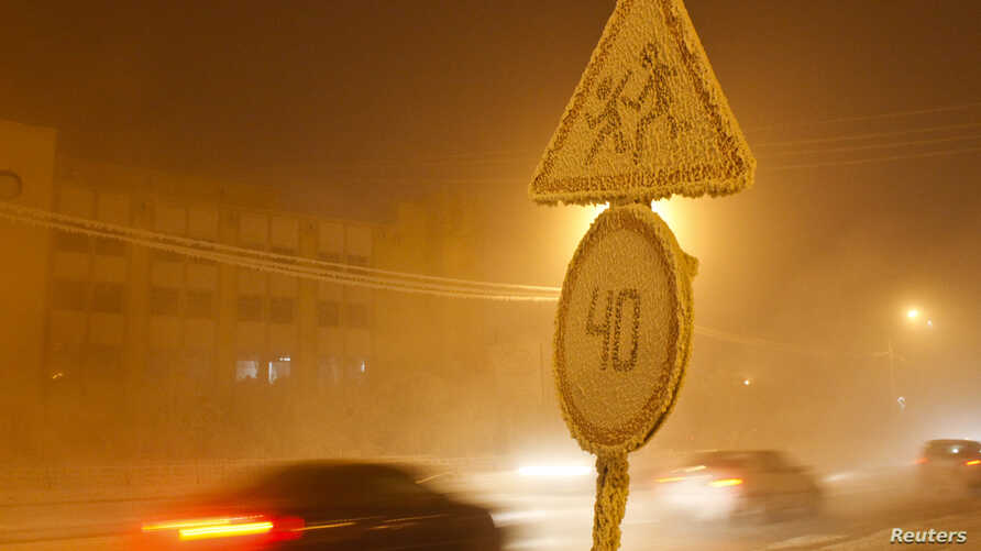 FILE - Cars pass by traffic signs covered with hoarfrost, with the air temperature at about minus 46 degrees Celsius (minus 50.8 degrees Fahrenheit), in the eastern Siberian city of Yakutsk in the Sakha (Yakutia) Republic, Jan. 16, 2013.