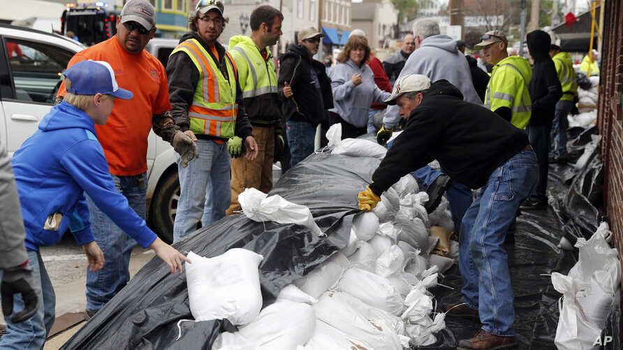 Volunteers place sandbags to protect buildings from potential floodwater, May 1, 2017, in Eureka, Mo.