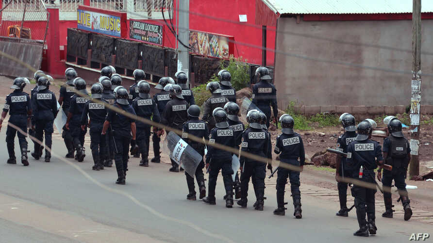 Cameroon police officials walk with riot shields on a street in the administrative quarter of Buea some 60kms west of Douala, Oct. 1, 2017.