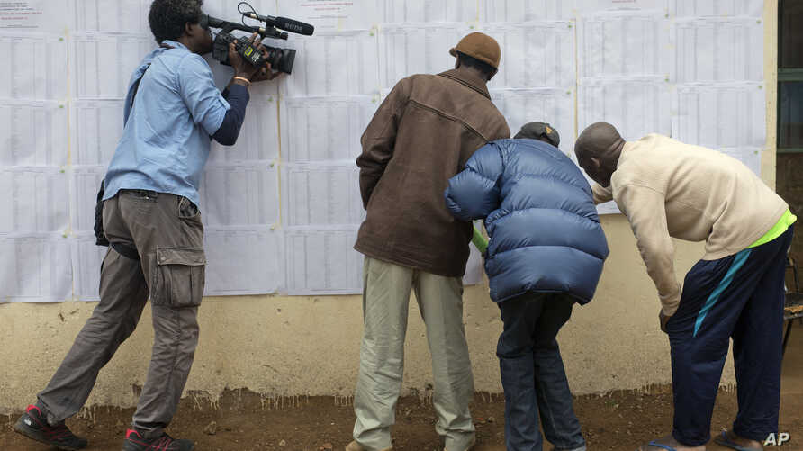 A television cameraman films Kenyans checking if their names are on the electoral lists at a polling station in the Kibera slum in Nairobi, Kenya, Monday Aug. 7, 2017. Kenyans are due to go to the polls on Aug. 8, to vote in presidential elections af