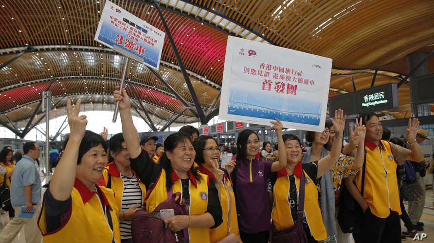 Tourists pose for a photograph at the departure hall of the China-Zhuhai-Macau-Hong Kong Bridge during the first day operation of the world's longest cross-sea project, which has a total length of 55 kilometers (34 miles), in Hong Kong, Oct. 24, 2018