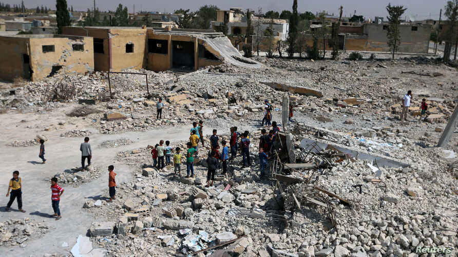 Pupils walk on debris of a damaged school in al-Saflaniyeh in eastern Aleppo's countryside, Syria, Sept. 17, 2017.