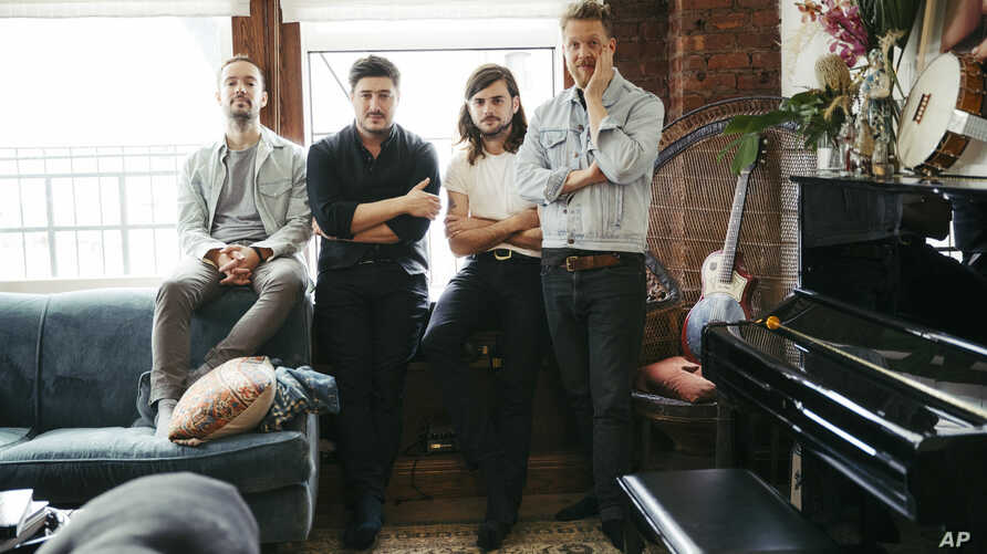 """FILE - Members of Mumford & Sons, from left, Ben Lovett, Marcus Mumford, Winston Marshall and Ted Dwane pose for a portrait in New York to promote their fourth album """"Delta,"""" Sept. 28, 2018."""