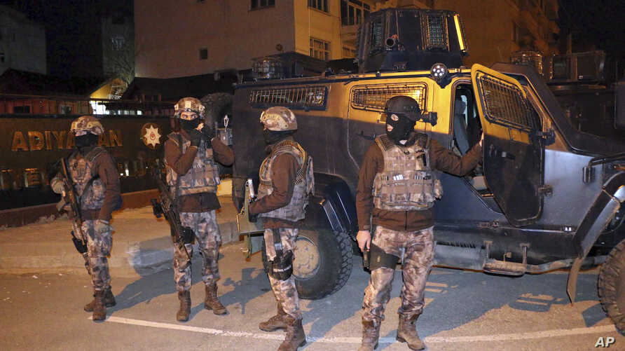 Turkish anti-terrorism police stand by their armoured vehicle during an operation to arrest people over alleged links to the Islamic State group, in Adiyaman, southeastern Turkey, early Sunday, Feb. 5, 2017.