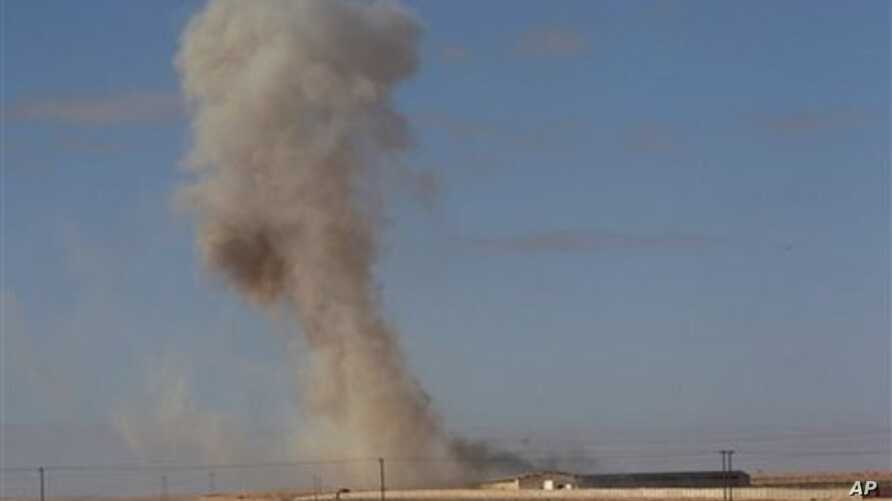 Smoke rises from a military army base which fell to anti-Gadhafi rebels following an air strike by Libyan warplanes in Ras Lanouf, eastern Libya, March 6, 2011
