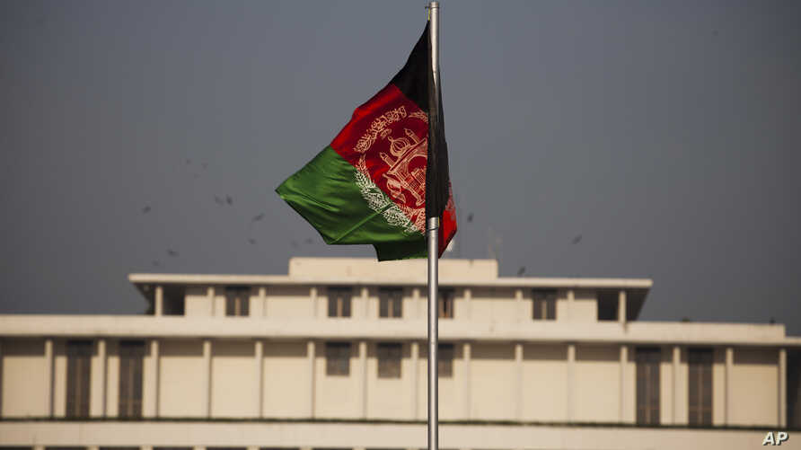 FILE - Afghanistan's flag is seen hoisted before the President House in Islamabad, Pakistan, Nov. 13, 2014, ahead of Afghan President Ashraf Ghani's first state visit to neighboring Pakistan.