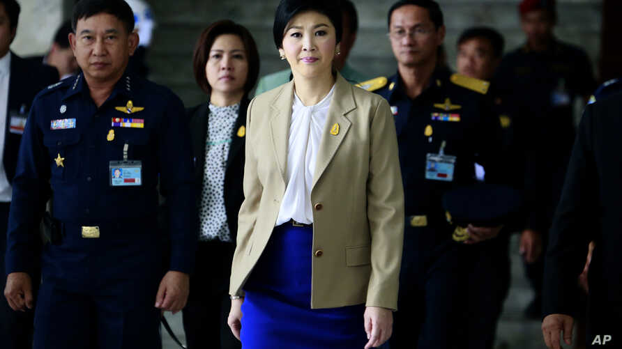 Prime Minister Yingluck Shinawatra, center, leaves the Thai Air Force headquarters after a cabinet meeting in Bangkok, Thailand,  Feb. 25, 2014.
