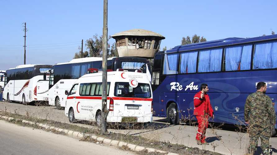 Syrian civilians in buses leave the Waer neighborhood, in the city of Homs, Syria, as part of a deal with local government forces in which dozens of of insurgents are also being allowed safe passage to areas in the country's north, Dec. 9, 2015.