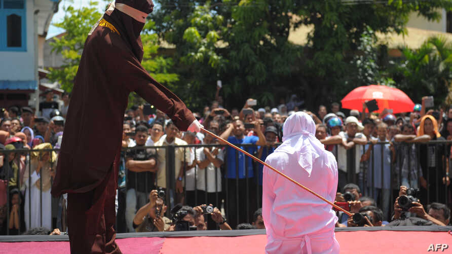 A religious officer canes an Acehnese youth onstage as punishment for dating outside marriage, which is against Sharia, or Islamic law, outside a mosque in Banda Aceh, Aug. 1, 2016. The strictly Muslim province, Aceh has become increasingly conservat