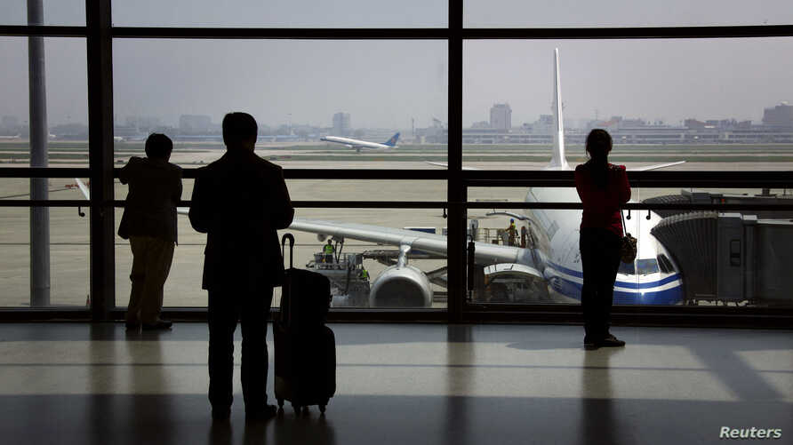 FILE - Passengers wait to board their plane at Shanghai's Hongqiao International Airport.