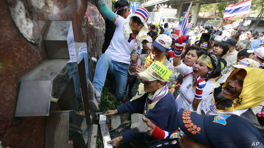 Anti-government protesters break the police sign outside police headquarters during a rally in Bangkok, Thailand, Jan. 22, 2014.