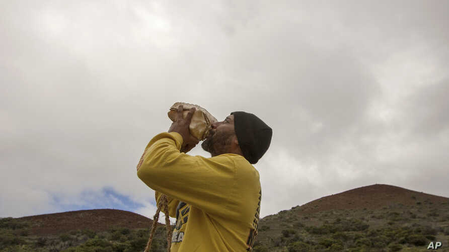 Kupono Mele-Ana-Kekua, 35, of Kaaaawa, Hawaii, blows a conch shell near the summit of Mauna Kea on Hawaii's Big Island, Monday, Aug. 31, 2015, protesting the planned construction of the Thirty Meter Telescope.