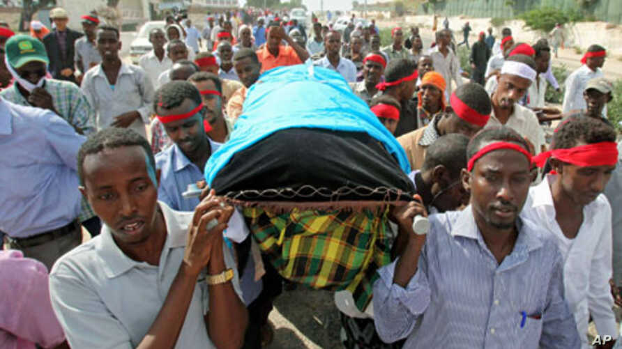 Somali journalists carry the slain body of their colleague, Abdisalan Sheikh Hasan, during his funeral in southern Mogadishu, Somalia, December 19, 2011.