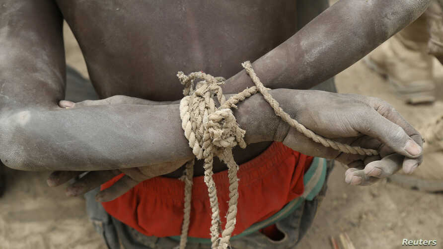 FILE - A prisoner, suspected of being a member of insurgent group Boko Haram, sits with his arms tied behind his back in the field base of Chadian soldiers in Gambaru, Nigeria, Feb. 26, 2015.