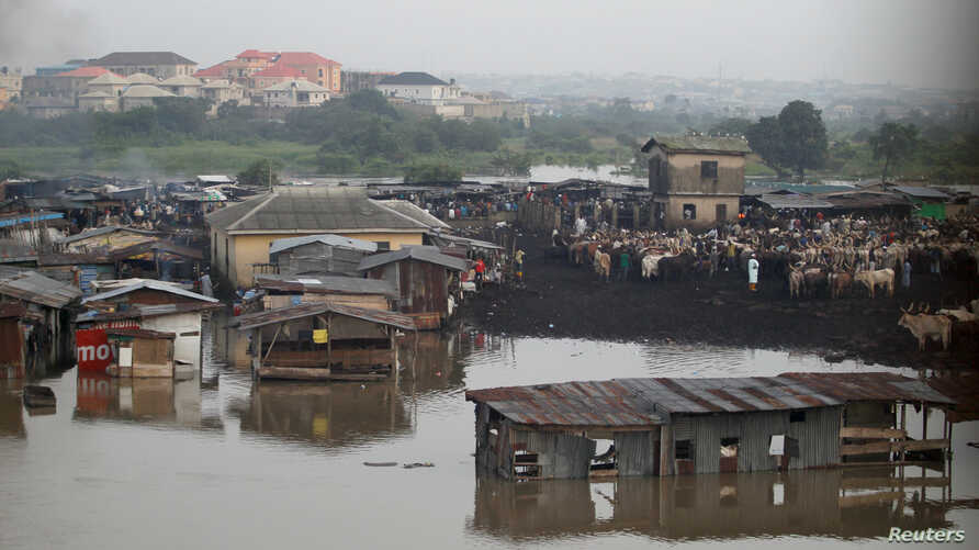 FILE - Makeshift stalls are seen submerged along river Ogun as it overflows its bank near a livestock market outside Nigeria's commercial capital Lagos, Oct. 6, 2016.
