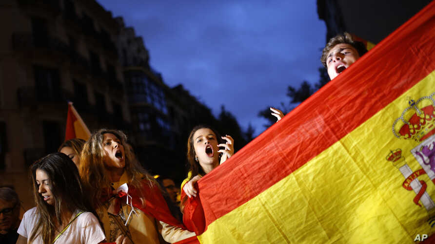 Anti-independence demonstrators waving Spanish flags shout slogans during a protest in Barcelona, Oct. 4, 2017.