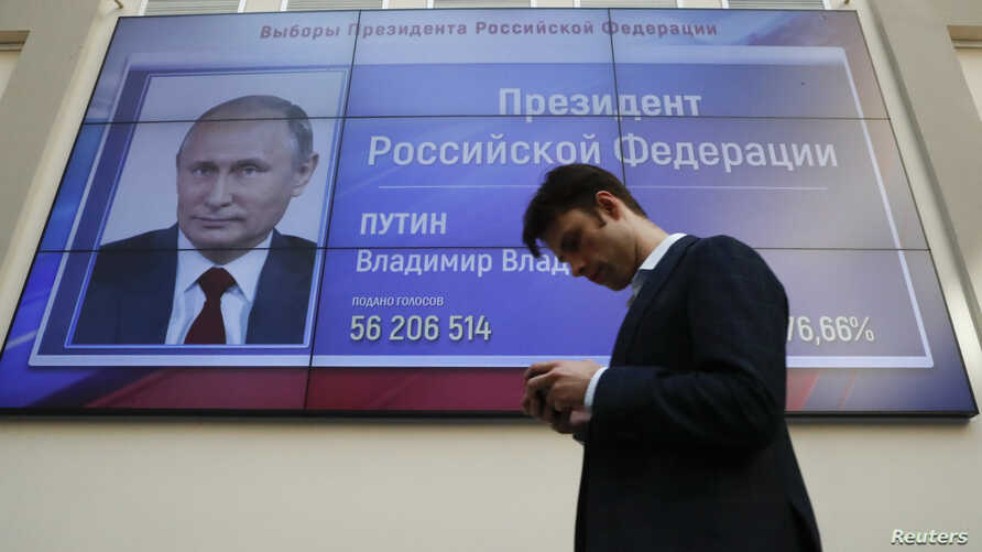 A man walks past a screen showing preliminary results of Russian President Vladimir Putin in the presidential election, at the headquarters of Russia's Central Election Commission in Moscow, March 19, 2018.