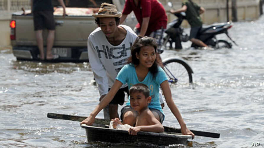 A Thai man pushes children sitting in a tub through floodwaters in Bangkok on October 21, 2011.