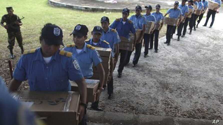 Police officers carry boxes filled with ballots to waiting vehicles that will distribute the material to polling centers, in Managua, Nicaragua, November 5, 2011.
