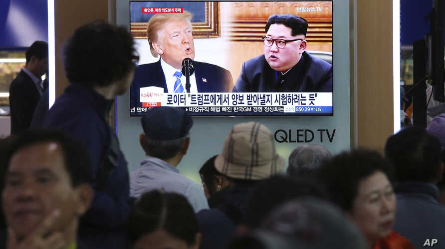 People watch a TV screen showing file footage of U.S. President Donald Trump, left, and North Korean leader Kim Jong Un during a news program at the Seoul Railway Station in Seoul, South Korea, May 16, 2018.