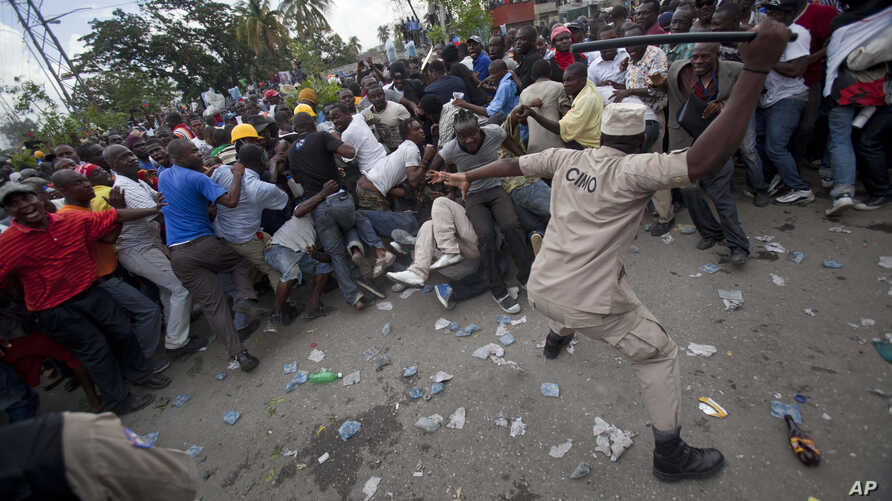 FILE: A police officer uses his baton to beat back supporters of Haiti's former President Jean-Bertrand Aristide who gathered outside the courthouse where Aristide arrived earlier in the day in Port-au-Prince, Haiti, Wednesday, May 8, 2013.