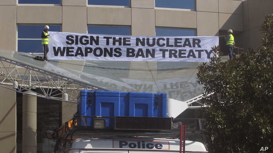 Two anti-nuclear weapons campaigners unfurl a banner, after they scaled the entrance awning of Australia's foreign ministry and onSept. 20, 2017, to protest the government's failure to endorse a United Nations' nuclear disarmament treaty.