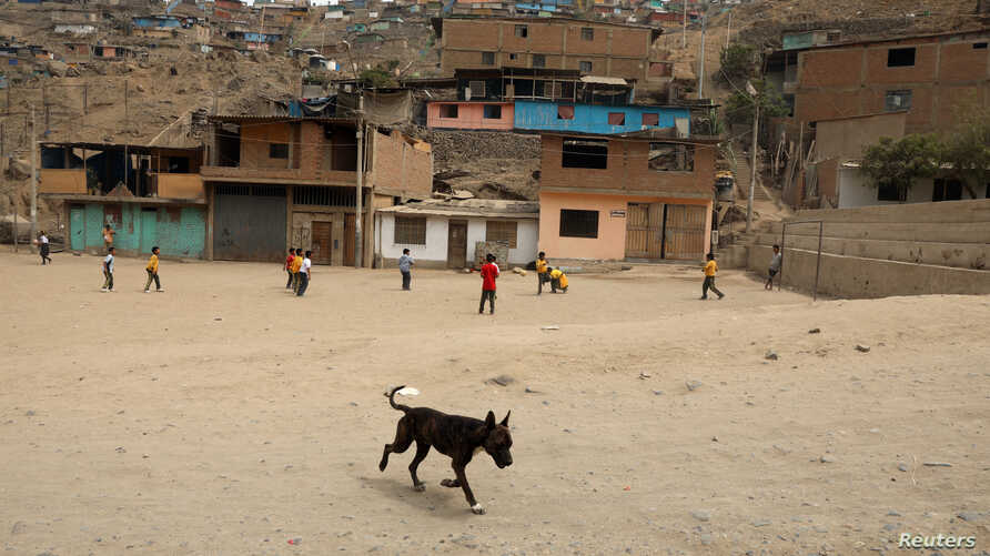 FILE - Children play soccer in the shanty town Nueva Esperanza on the outskirts of Lima, Peru, April 4, 2018.
