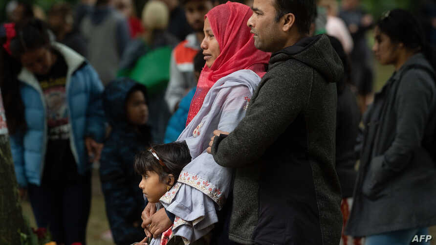 A Muslim family stands across the road from the Dean Street mosque when worshipers were gunned down in Christchurch on March 17, 2019.