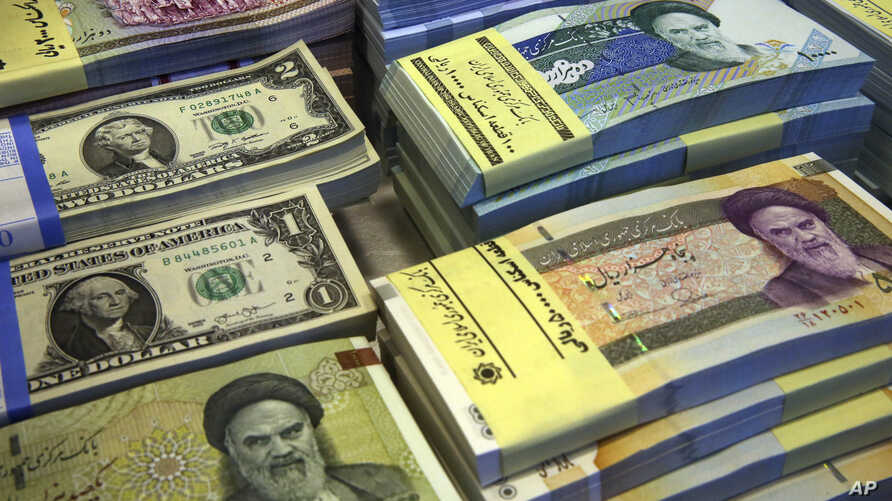FILE- Iranian and U.S. banknotes are on display at a currency exchange shop in downtown Tehran, Iran, April 4, 2015. In recent months, Iran has been beset by economic problems despite the promises surrounding the 2015 nuclear deal it struck with worl
