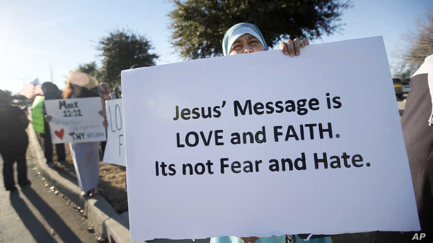A woman who asked not to be identified holds a sign as she joins hundreds of supporters outside the Curtis Culwell Center where a Muslim conference against terror and hate was scheduled, Jan. 17, 2015, in Garland, Texas.