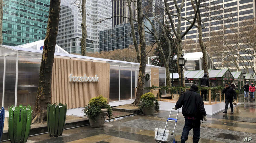 "FILE - People walk by a Facebook ""pop-up"" trailer in New York's Bryan Park, part of a one-day public event with Facebook employees answering questions about privacy settings and other issues, Dec. 13, 2018."