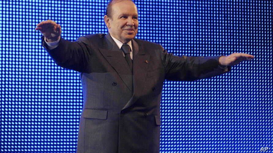 FILE - In this Feb.12 2009 photo, Algerian President Abdelaziz Bouteflika waves during a rally in Algiers. People of all ages marched  March 15, 2019, through Algeria's capital and other cities amid heavy security for what could be decisive protests