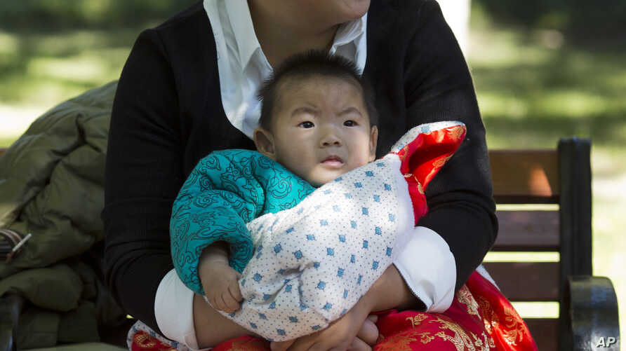 A child is wrapped up against the cold at a park in Beijing, China, Oct. 30, 2015.  Shares of companies making diapers, baby strollers and infant formula were getting a boost Friday from China's decision to scrap its decades-old one-child policy.
