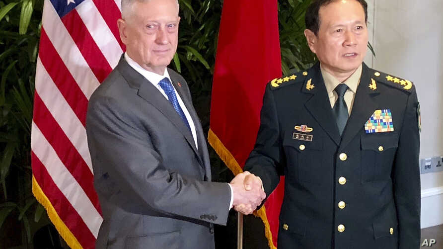 U.S. Defense Secretary Jim Mattis, left, meets with Chinese Defense Minister Wei Fenghe in Singapore, Oct. 18, 2018.