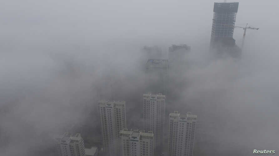 Buildings are seen shrouded in heavy haze at Qingdao development zone, Shandong province, February 25, 2014. China's north is suffering a pollution crisis, with the capital Beijing itself shrouded in acrid smog. Authorities have introduced anti-pollu...
