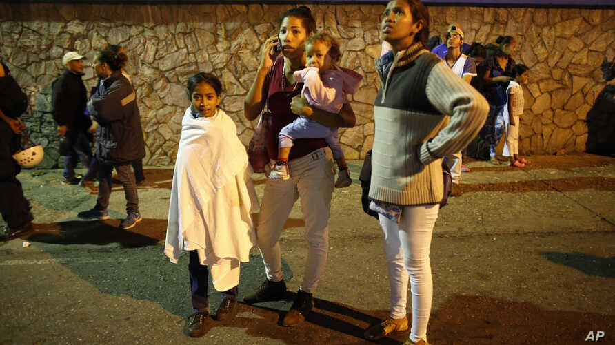 """Residents stand outside their apartments in a street near the """"Tower of David"""" skyscraper, which suffered an inclination after a powerful earthquake shook eastern Venezuela, causing buildings to be evacuated in the capital of Caracas, Aug. 21, 2018."""