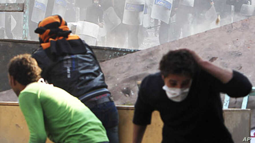 Protesters and police throw stones during clashes near Tahrir Square in Cairo, November 23, 2011.