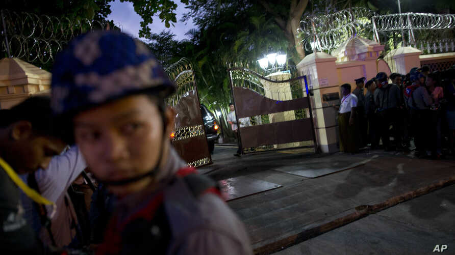 A security officer closes the gate at Myanmar's Bishop's house after a convoy of vehicles carrying Myanmar's military leader, Gen. Min Aung Hlaing, enters for a meeting with Pope Francis, Nov. 27, 2017, in Yangon, Myanmar.