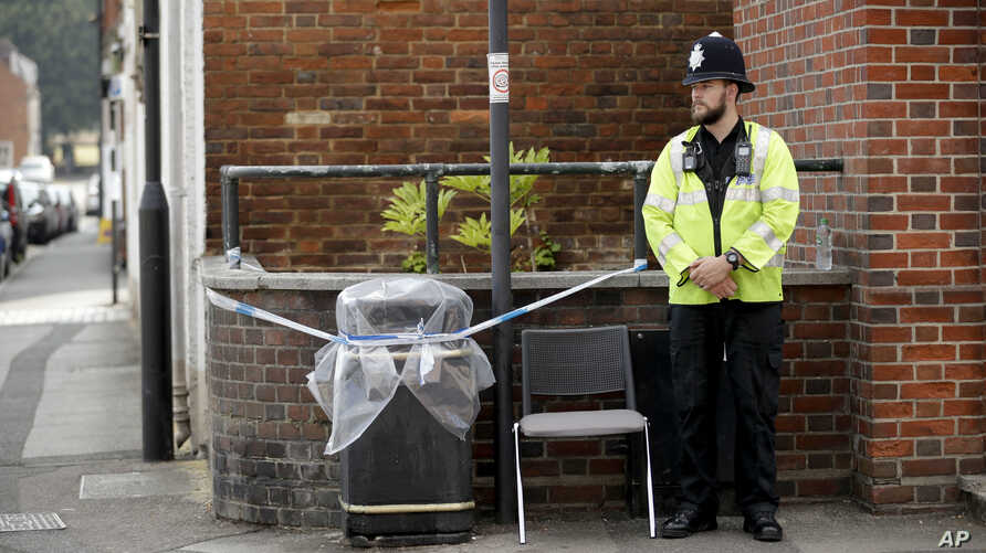 A British police officer guards a cordon around a plastic covered rubbish bin near John Baker House for homeless people in Salisbury, England, Thursday, July 5, 2018.