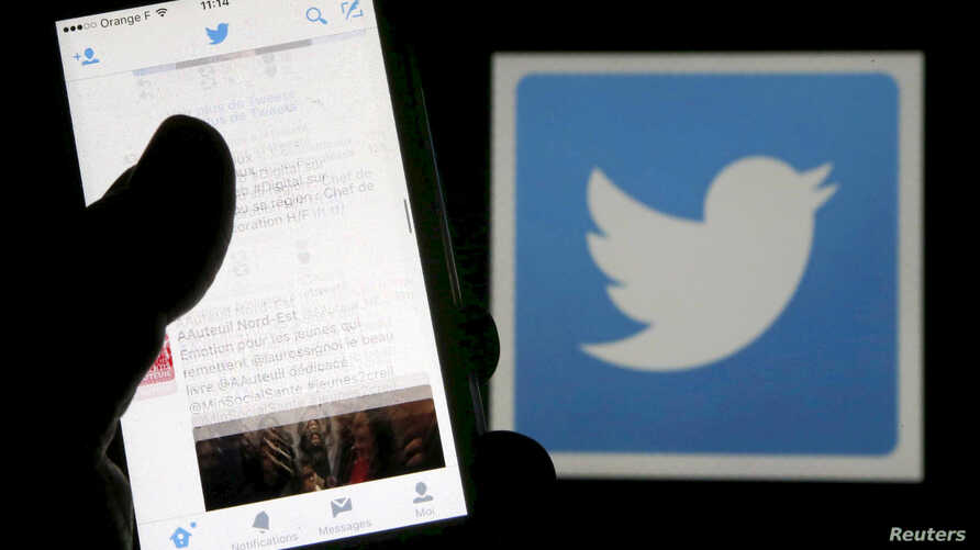 FILE - A man reads tweets on his phone in front of a displayed Twitter logo in Bordeaux, southwestern France.