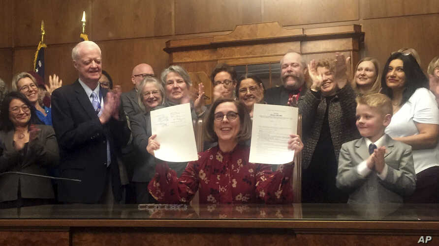Oregon Gov. Kate Brown holds up a signed rent control bill, Feb. 28, 2019, at the State Capitol in Salem. The state is now the first in the nation to impose mandatory rent control.